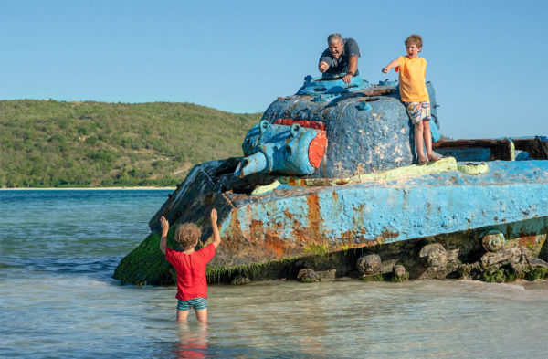 Two boys and their dad play on an abandoned tank in shallow water