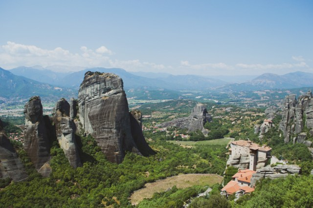 A monastery in the right foreground of a landscape photo to Meteora, Greece.