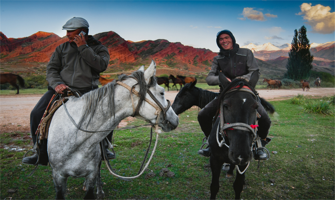 Nomadic horsemen in Central Asia pose in front of livestock and mountains.