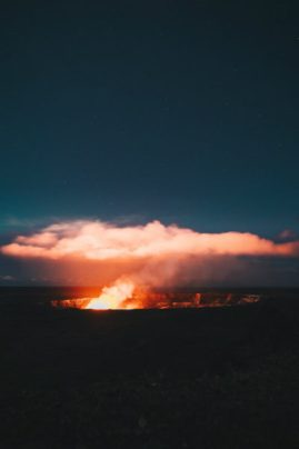 A smoking volcano within the Hawaii Volcanoes National Park at night with pink clouds