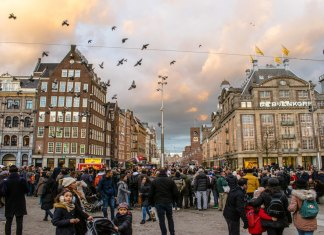 tourists gather on dam square in Amsterdam
