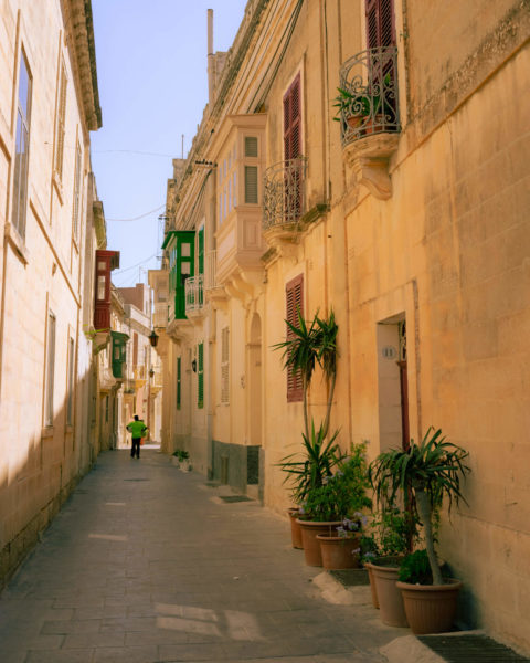 a tourist walks down an alleyway in malta