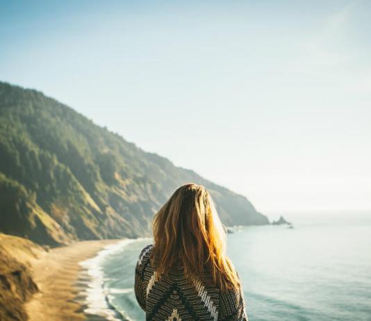 Woman overlooks ocean coastline
