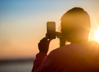 woman with smartphone sunset