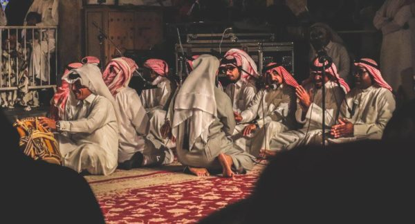 men in a doha souk sit in a circle