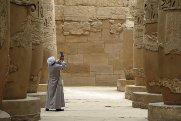 a man takes a picture in karnak temple complex