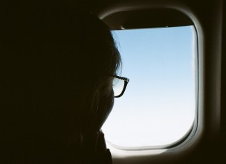 person looking out window of plane