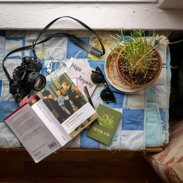 camera and books spread on blanket