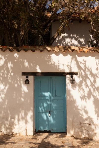 solitary blue door in white wall villa de leyva colombia