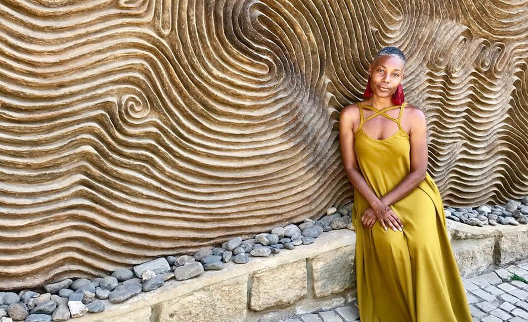 woman in yellow dress sitting against wall art