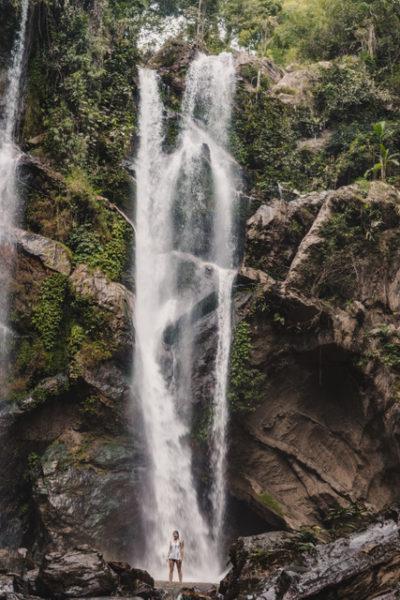 woman at base of waterfall