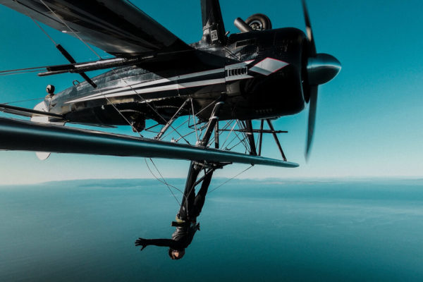 plane flying upside down with man wing walking