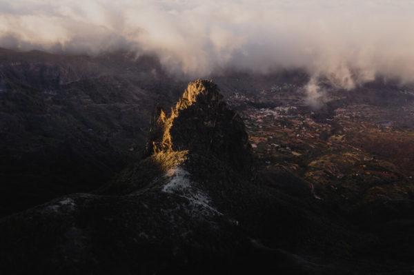 lone mountain peak rising into clouds