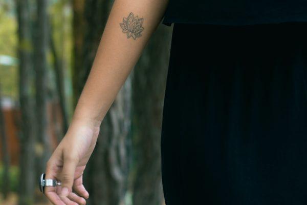 lotus flower tattoo on woman's forearm
