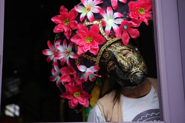 person wearing black and gold mask with flowery headgear