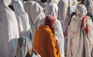 orange-robed worshipper amongst others in white robes