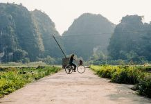 cyclist on dirt road through mountains