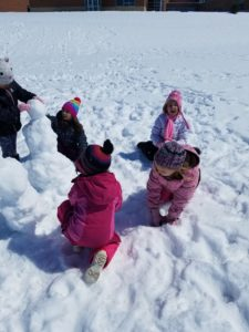 Students building two small snowman