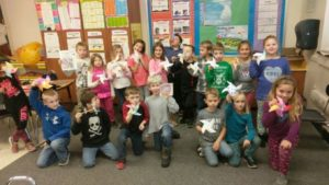 Students showing the pinwheels they made in class.