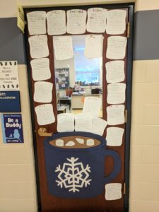 Door decorated with a mug of hot chocolate and marshmallows.  The marshmallows have New Year's resolutions written on them.