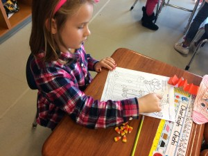 student doing math with candy corn