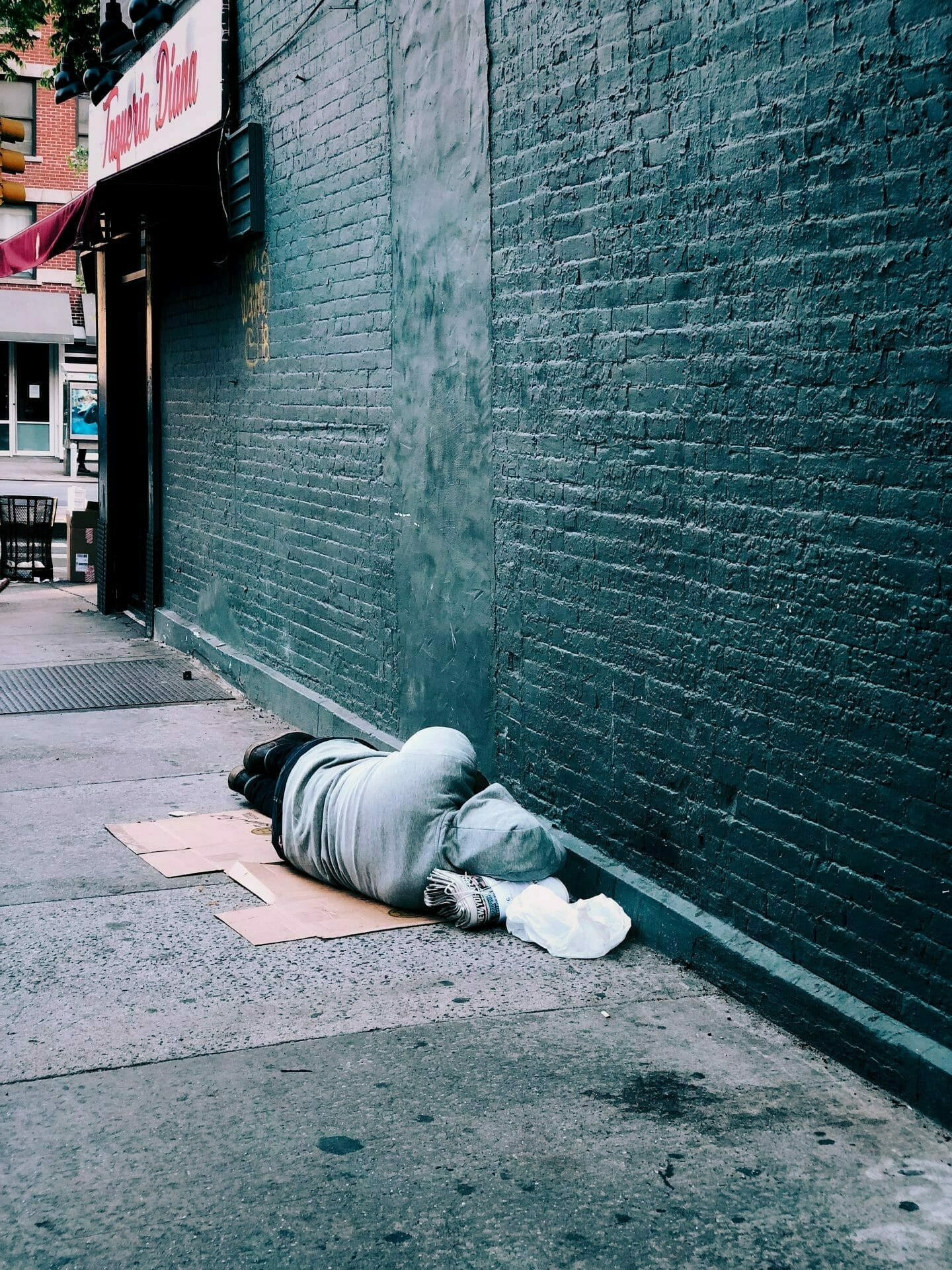Picture of homeless person asleep on sidewalk for Real Estate News for Investors Podcast Episode #719
