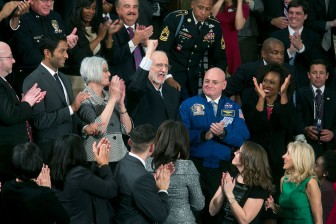 """Recently released from prison in Cuba, Alan Gross pumps his fist in the air from First Lady Michelle Obama's box after President Obama acknowledged him at the State of the Union address at the U.S. Capitol."" (Official White House Photo By Chuck Kennedy)"