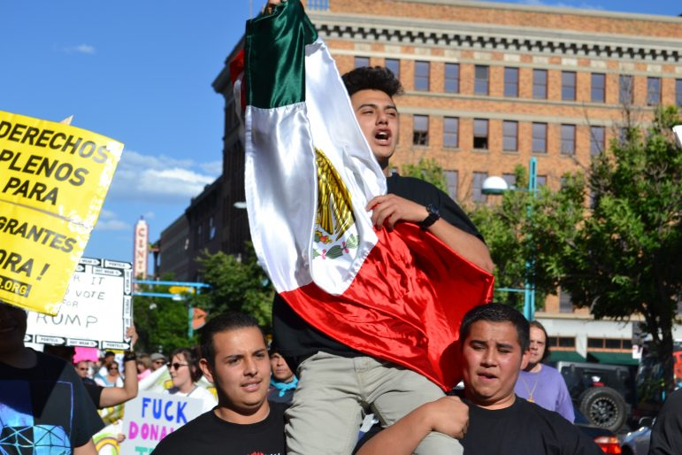 Protesters carrying a Mexico flag while marching in downtown Albuquerque.