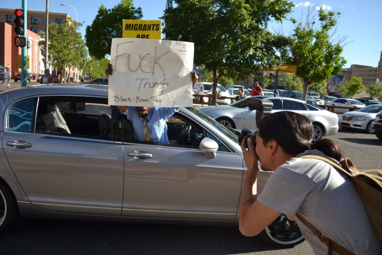 An anti-Trump protester leans out the car window as protesters march in downtown Albuquerque.