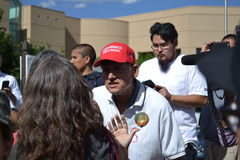 "A Donald Trump supporter with a ""Make America Great Again"" hat argues with an anti-Trump protester."