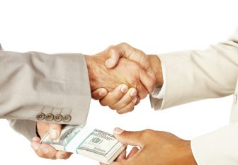 Close-up of a business people handshaking and bribing against white background