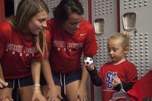 Teammates Sam Goodwin, Christen Cahill and Rylie Laber (left to right) hang out in the locker room.ARACELY JIMENEZ/THE STATESMAN