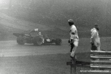 Jackie Stewart passes corner workers in their wet weather gear