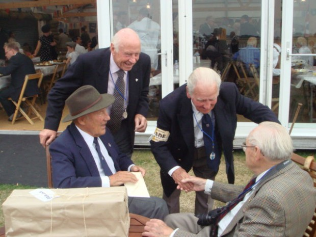 Moss, left, in the Drivers' Mess, with friend Mike Wheatley behind, introducing famed Jaguar test driver to John Brierley. Brierley, 95, ran the pub where Moss used to stay near Goodwood 60 years ago, He presented Moss with a OO gauge locomotive model which took him 18 months to build for Moss' birthday.