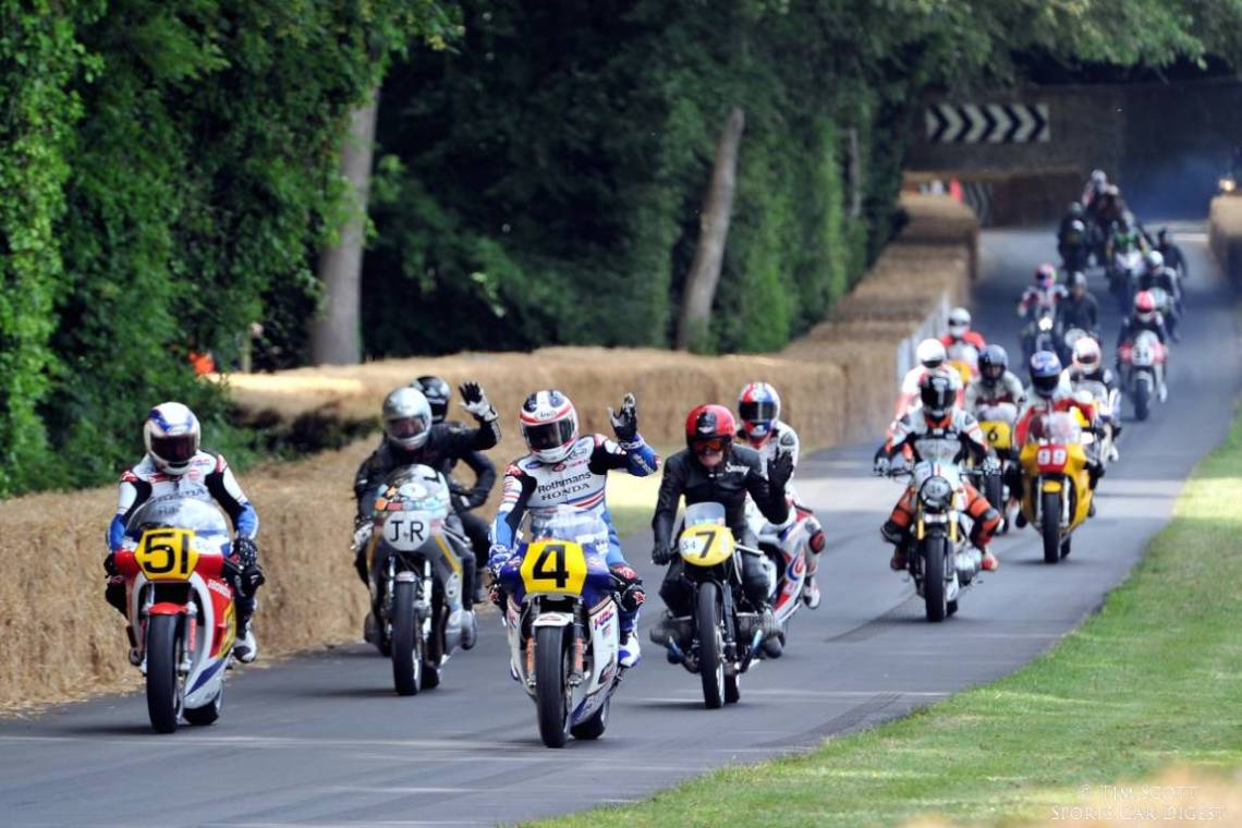 Wayne Gardner leads bikes down the Goodwood hill climb