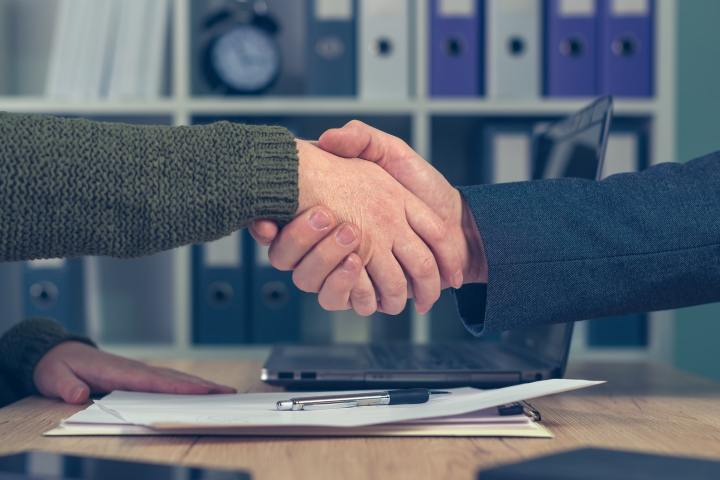 Man and woman shaking hands over business agreement