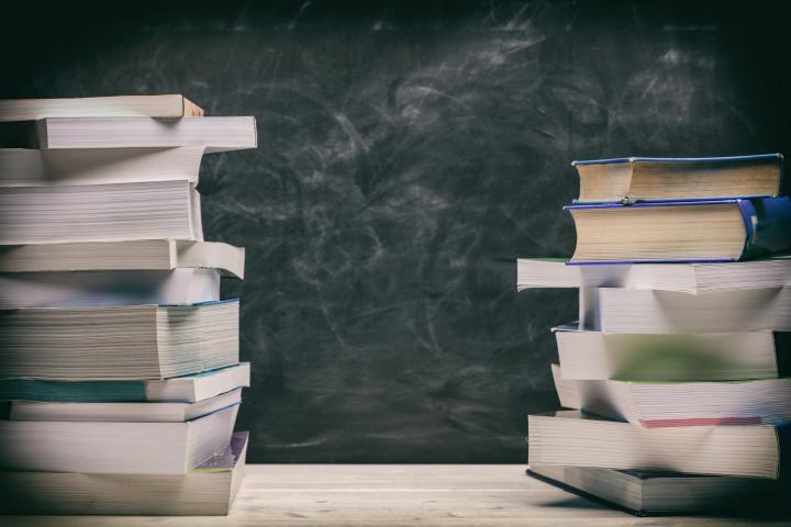 Books stacks on blackboard background