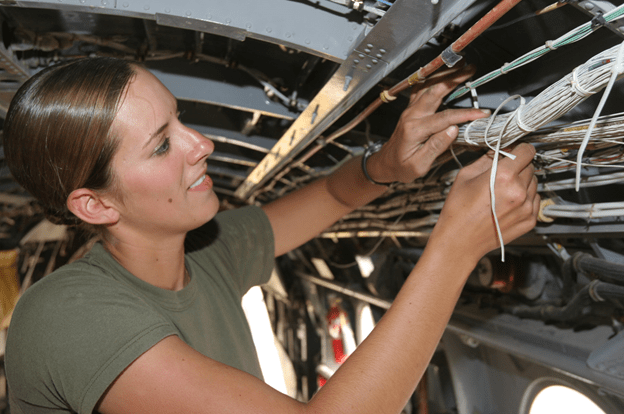 Female mechanic working with wiring bundle