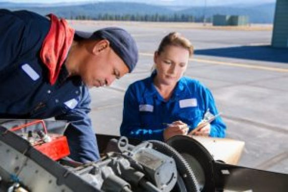 Female mechanic assisting male mechanic on aircraft engine repair