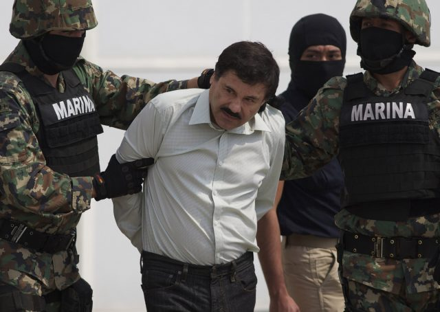 "FOR USE AS DESIRED, YEAR END PHOTOS - FILE - In this Saturday, Feb. 22, 2014 photo, Joaquin ""El Chapo"" Guzman is escorted to a helicopter in handcuffs by Mexican navy marines at a navy hanger in Mexico City, Mexico. Guzman, the head of Mexico's Sinaloa Cartel, was captured alive overnight in the beach resort town of Mazatlan. (AP Photo/Eduardo Verdugo, File)"