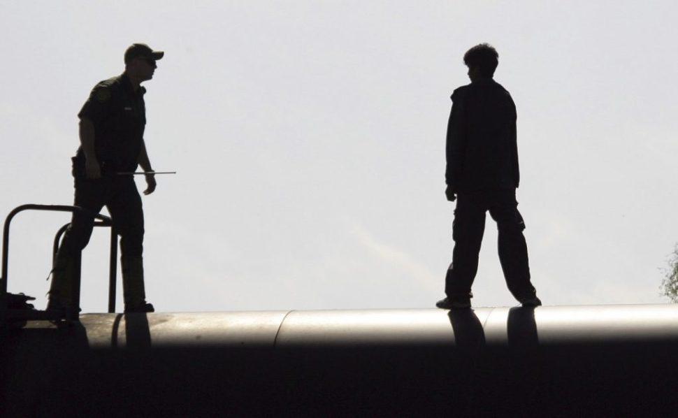 policía migración detiene a niño sobre vagón