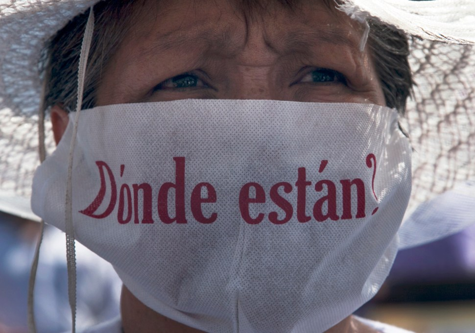 """A mother with a face mask that reads in Spanish """"Where are they?"""" marches along with hundreds of other mothers holding images of their missing relatives during Mother's Day, in Mexico City, Sunday, May 10, 2015. Mothers and other relatives of persons gone missing in the fight against drug cartels and organized crime are demanding that authorities locate their loved ones. (AP Photo/Marco Ugarte)"""