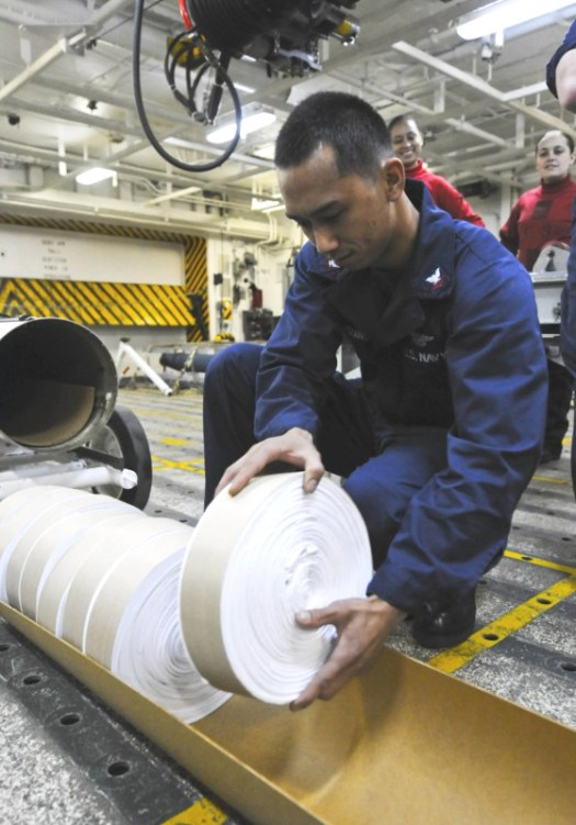A sailor packs rolls of leaflets into a PDU-5/B on board the aircraft carrier USS <em data-recalc-dims=
