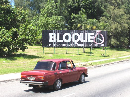 A car drives past a billboard in Havana protesting the United States' embargo of Cuba in 2016.
