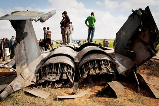 Civilians stand on the wreck of a US Air Force F-15E Strike Eagle that crashed in Libya in 2011
