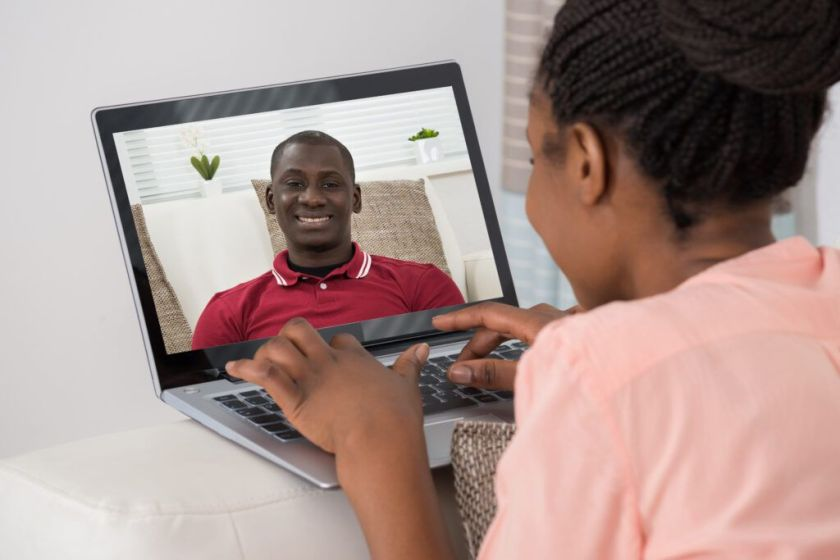 Close-up Of Young African Woman Video Chatting With Man On Laptop