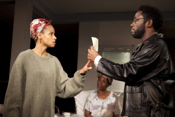 Moxie (Lakisha Michelle May) and Abasiama (Chinasa Ogbuagu) look on in wonder and disbelief as Disciple (Chinaza Uche) works his magic on a job application.
