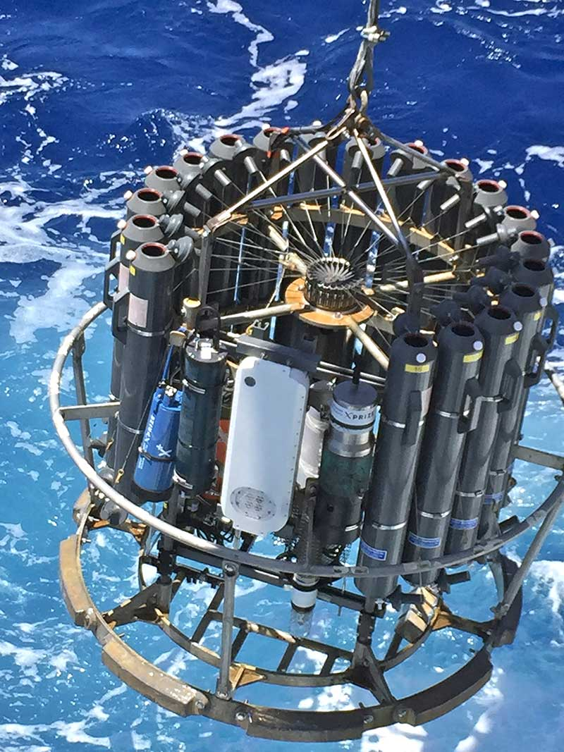 "Researchers lower a ""rosette package"" to the bottom of the ocean to gather water samples. (NOAA)"
