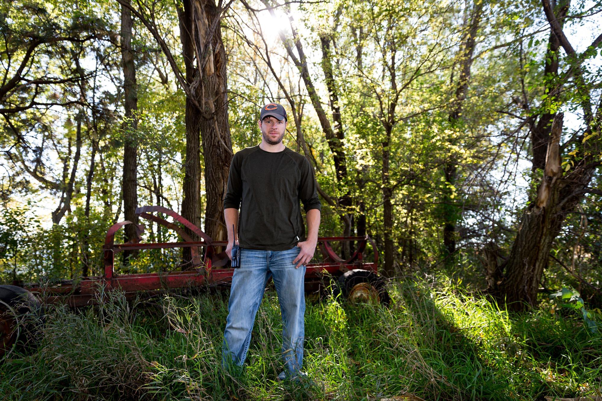 Graham Christensen at the edge of the shelterbelt on his family's farm in Lyons, Nebraska.