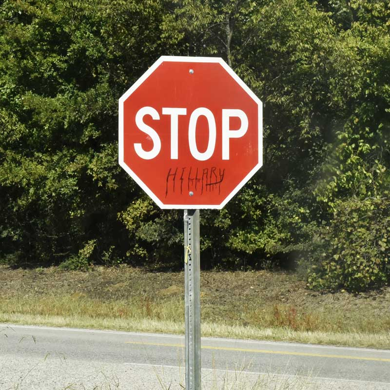 A stop sign is graffitied to read